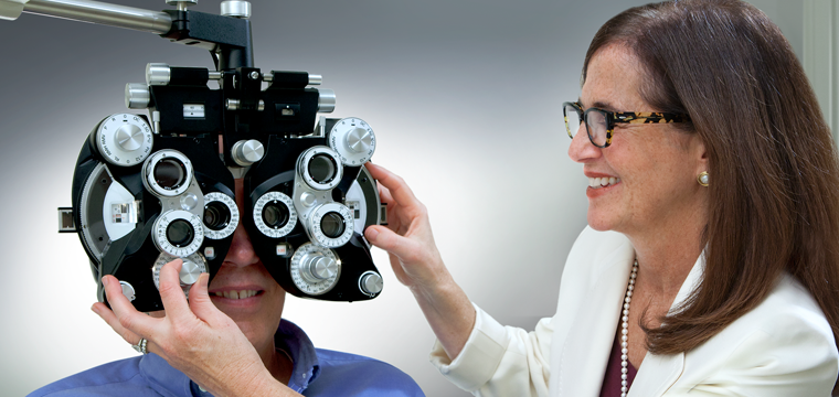 female eye doctor giving eye exam to male patient